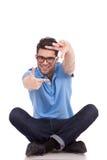 Hombre joven que se sienta haciendo el marco Foto de archivo