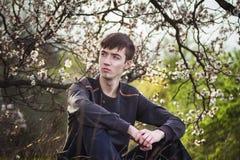 Hombre joven que se sienta por el árbol floreciente Fotos de archivo libres de regalías
