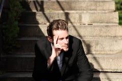 Hombre joven que se sienta preguntarse del exterior fotografía de archivo