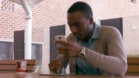 Hombre joven que se sienta que usa smartphone y la tableta