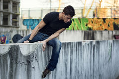 Hombre joven que se sienta y que equilibra en la pared, mirando abajo Imagenes de archivo