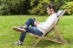 Hombre joven que se sienta y que escucha la música en parque verde Fotografía de archivo