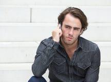 Hombre joven que se sienta y que habla en el teléfono móvil Imagen de archivo