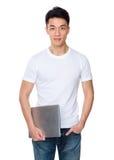 Hombre joven que se sostiene con el ordenador portátil Fotografía de archivo libre de regalías