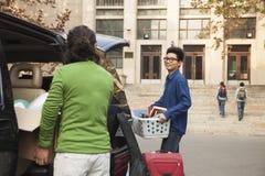 Hombre joven que se traslada a dormitorio en campus de la universidad Imágenes de archivo libres de regalías