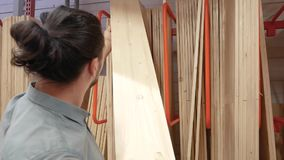 Hombre joven que selecciona a los tableros de madera en una ferretería o un almacén metrajes