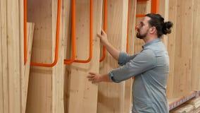 Hombre joven que selecciona a los tableros de madera en una ferretería o un almacén almacen de metraje de vídeo