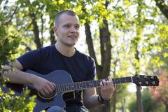 Hombre joven que sienta y que toca la guitarra en el parque Foto de archivo libre de regalías