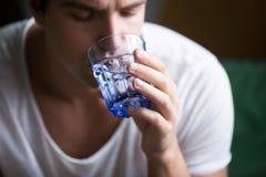 Hombre joven que siente sediento deshidratado llevando a cabo el wate de consumición del vidrio Foto de archivo