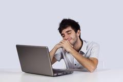 Hombre joven que soña delante de su computadora portátil Foto de archivo