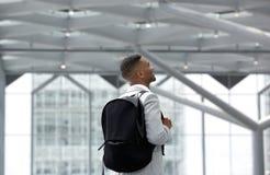 Hombre joven que sonríe con el bolso en el aeropuerto Fotos de archivo