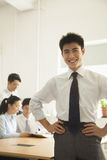 Hombre joven que sonríe en la oficina, retrato Imagen de archivo libre de regalías