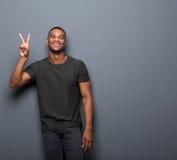 Hombre joven que sonríe mostrando el signo de la paz de la mano Fotos de archivo libres de regalías