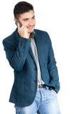 Hombre joven que sonríe y que habla en el teléfono elegante Fotos de archivo libres de regalías
