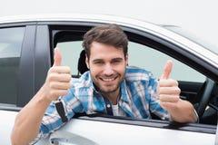 Hombre joven que sonríe y que muestra los pulgares para arriba Imagen de archivo libre de regalías