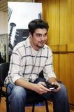 Hombre joven que sonríe y que sostiene la palanca de mando de Playstation fotografía de archivo