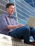 Hombre joven que sonríe en el ordenador portátil al aire libre Imágenes de archivo libres de regalías