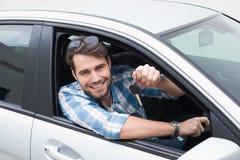 Hombre joven que sonríe en la cámara que muestra llave Imagenes de archivo
