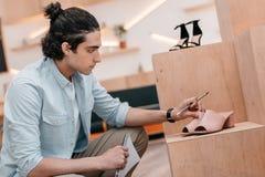 Hombre joven que sostiene el cuaderno con el lápiz mientras que mira los zapatos y trabaja en boutique Fotografía de archivo libre de regalías