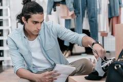 Hombre joven que sostiene el cuaderno con el lápiz mientras que mira los zapatos y trabaja en boutique Fotos de archivo libres de regalías