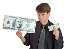 Hombre joven que sostiene el dinero grande y pequeño Imagen de archivo