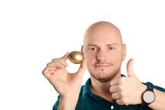 Hombre joven que sostiene el huevo de oro a la cámara, sintiéndose confiada imagenes de archivo