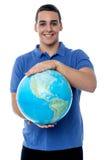 Hombre joven que sostiene el mapa del globo Fotos de archivo