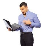 Hombre joven que sostiene el ordenador portátil con la expresión sorprendida aislado en w Imágenes de archivo libres de regalías
