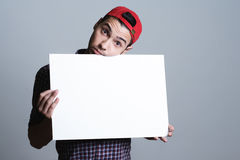 Hombre joven que sostiene el papel en blanco en un estudio Imagen de archivo libre de regalías