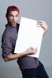 Hombre joven que sostiene el papel en blanco en un estudio Imágenes de archivo libres de regalías