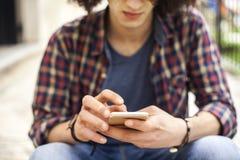 Hombre joven que sostiene el teléfono móvil Fotos de archivo