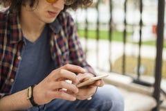 Hombre joven que sostiene el teléfono móvil Foto de archivo libre de regalías