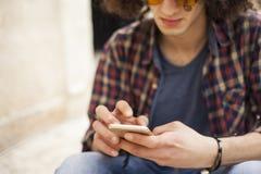 Hombre joven que sostiene el teléfono móvil Imagen de archivo libre de regalías