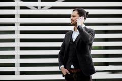Hombre joven que sostiene el teléfono móvil, haciendo una llamada, hablando en, Imágenes de archivo libres de regalías