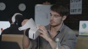 Hombre joven que sostiene gafas de la realidad virtual en oficina oscura creativa metrajes