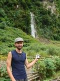 Hombre joven que sostiene GPS cerca de la cascada en Nepal Fotos de archivo libres de regalías