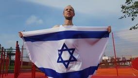 Hombre joven que sostiene la bandera nacional de Israel almacen de metraje de vídeo