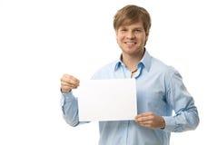 Hombre joven que sostiene la hoja en blanco Fotos de archivo libres de regalías