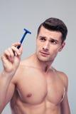 Hombre joven que sostiene la maquinilla de afeitar Foto de archivo libre de regalías