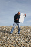 Hombre joven que sostiene la tarjeta blanca Imágenes de archivo libres de regalías