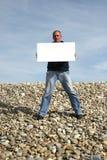 Hombre joven que sostiene la tarjeta blanca Imagen de archivo libre de regalías