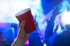 Hombre joven que sostiene la taza roja del partido en sala de baile del club nocturno Envase del alcohol a disposición en disco E Foto de archivo libre de regalías