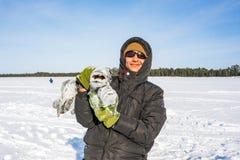 Hombre joven que sostiene pescados para coger una pesca grande del hielo del lucio imagen de archivo