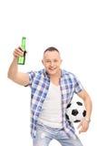 Hombre joven que sostiene un fútbol y una botella de cerveza Imagen de archivo