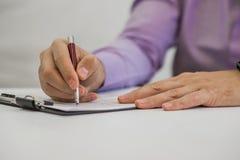 Hombre joven que sostiene un lápiz, escribiendo en un papel en el diario Fotografía de archivo