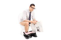 Hombre joven que sostiene un periódico asentado en retrete Fotografía de archivo libre de regalías