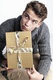 Hombre joven que sostiene un regalo envuelto oro Fotos de archivo