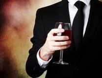Hombre joven que sostiene un vidrio de vino rojo foto de archivo libre de regalías