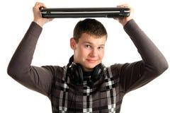 Hombre joven que sostiene una computadora portátil adentro sobre su cabeza Imagen de archivo libre de regalías