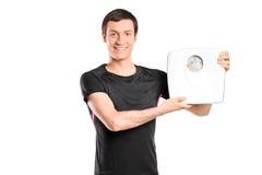Hombre joven que sostiene una escala del peso Imagen de archivo libre de regalías